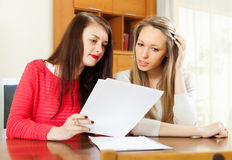 Ernstige vrouwen die documenten lezen Stock Foto