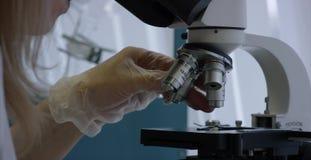 Ernstige werker uit de gezondheidszorg die chemisch element in laboratorium bestuderen Sluit omhoog van microscopische lens Steek stock videobeelden