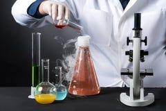 Ernstige werker uit de gezondheidszorgstudies met buizen en flessen in laboratorium Stock Foto