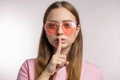 Ernstige youn modieuze vrouw die in roze zonnebril een stil gebaar maken stock afbeelding