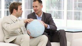 Ernstige zakenlieden die een aardse bol bekijken stock videobeelden