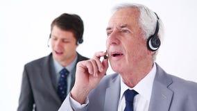 Ernstige zakenlieden die hoofdtelefoons met behulp van stock video
