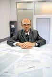 Ernstige zakenman die in bureau werkt Stock Foto