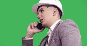 Ernstige zakenman in een witte bouwhelm die op een mobiele telefoon op groene chroma zeer belangrijke achtergrond spreken stock footage