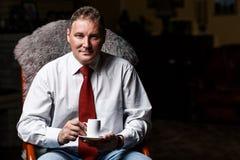 Ernstige zakenman op middelbare leeftijd met koffiekop stock fotografie
