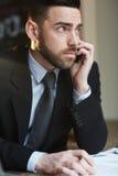 Ernstige Zakenman Speaking op Telefoon in Bureau royalty-vrije stock foto