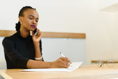 Ernstige zekere jonge Afrikaanse of zwarte Amerikaanse bedrijfsvrouw op telefoon die nota's in bureau nemen Stock Foto