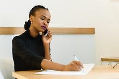 Ernstige zekere jonge Afrikaanse of zwarte Amerikaanse bedrijfsvrouw op telefoon die nota's in bureau nemen Royalty-vrije Stock Afbeeldingen