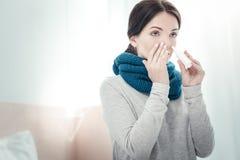 Ernstige zieke vrouw die neusnevel het raken gebruiken aan haar neus royalty-vrije stock afbeelding