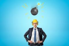 Erntebild des Geschäftsmannes im gelben Schutzhelm mit Gehörschutzkapseln, stehend mit den Händen auf Hüften und rundes Bombenfal stockfotografie