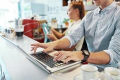 Erntecafeteriainhaber, der Laptop am Zähler verwendet lizenzfreies stockbild