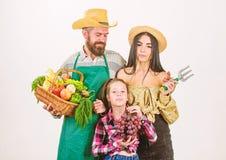 Erntefestkonzept Eltern und Tochterlandwirte feiern Erntefeiertag Rustikale Artlandwirte der Familie stolz auf stockfotografie