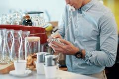 Erntemann, der Auftrag über Telefon in der Cafeteria nimmt stockbilder