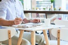 Erntemann mit Laptop und Papieren in der Kaffeestube stockbilder