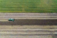 Erntemaschine erntet eine Ernte auf einem Gebiet nahe bei einem grünen Feld mit Mais ukraine Schattenbild des kauernden Geschäfts Stockfotografie