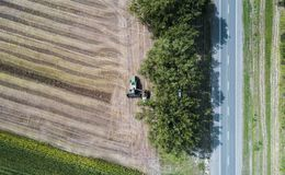Erntemaschine erntet eine Ernte auf einem Gebiet nahe bei einem grünen Feld mit Mais ukraine Schattenbild des kauernden Geschäfts Lizenzfreies Stockbild