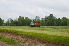 Erntemaschine sammelt trockenes Gras zum LKW Lizenzfreie Stockbilder
