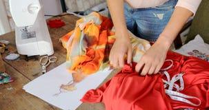 Erntenäherin, die Gewebe für Kleid wählt Stockbilder