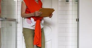 Ernten Sie die Mutter, die Baby im Riemen hält, der an Tablette arbeitet stock video footage