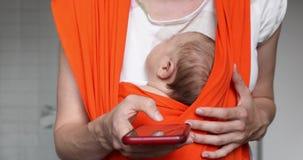 Ernten Sie Mutter mit Baby im Riemen, der Smartphone hält stock footage
