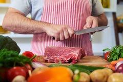 Ernten Sie Schuss von den Händen, die Messer für den Schnitt des Fleisches schärfen lizenzfreies stockfoto