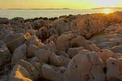 Erodded vulkanische rotsen op de kust van het Adriatische overzees in zonsondergangtijd Stock Afbeelding