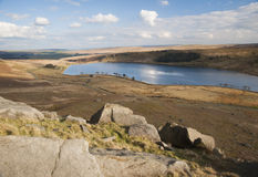 Eroded boulders on yorkshire moorland. Exposed and eroded millstone grit boulders laying on a hillside overlooking a yorkshire moorland reservoir on a sunny Stock Image