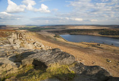 Eroded boulders on yorkshire moorland. Exposed and eroded millstone grit boulders laying on a hillside overlooking a yorkshire moorland reservoir on a sunny Royalty Free Stock Photo
