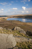 Eroded boulders on yorkshire moorland. Exposed and eroded millstone grit boulders laying on a hillside overlooking a yorkshire moorland reservoir on a sunny Royalty Free Stock Images