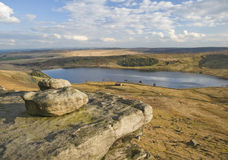 Eroded boulders on yorkshire moorland. Exposed and eroded millstone grit boulders laying on a hillside overlooking a yorkshire moorland reservoir on a sunny royalty free stock photography