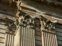 Eroded corinthian pilasters. Close up of capitals of corinthian pilasters on the wall of a deserted building Royalty Free Stock Image