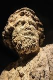 Really eroded head of Poseidon - god of the sea earthquakes storms, and horses - that was underwater for a long time and is pitted royalty free stock photo
