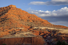 Eroded red mountain with sparse vegetation Royalty Free Stock Photo