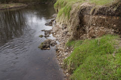 Eroded riverbank after winter flood, Reddish Vale Manchester Eng. Land Stock Photo