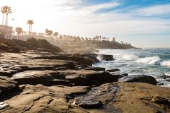 Eroded Rock Formations and Cliffs at Windansea Beach. Eroded rock formations and cliffs on a hazy morning at Windansea Beach in La Jolla, California Stock Image