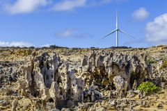 Eroded rock formations and wind turbines - renewable energy and earth conservation concept. Stock Image
