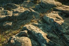 Eroded rocks with green grass on sunset. Close-up of eroded rocks with green grass on sunset at Guarda. This friendly and well-kept medieval town is the highest stock photos