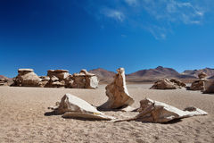 Eroded rocks laying in sand desert of Andes Royalty Free Stock Photos