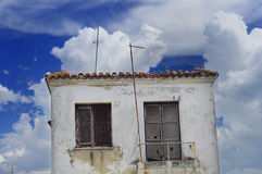Eroded tiny house. Small tropical house with eroded walls against blue sky Stock Photo