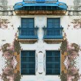 Eroderad gammal havannacigarrfasad med blåa fönster royaltyfri fotografi