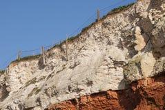 Eroding Cliffs at Hunstanton, Norfolk, UK. A fence falling over eroding cliffs at Hunstanton, Norfolk, UK Stock Image