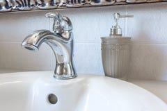 Erogatori dello sciampo e del sapone sul lavandino del rubinetto di acqua con il rubinetto nel bagno costoso del sottotetto fotografia stock libera da diritti
