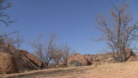 Erongo moutain landscape with rocks and dry bushes. Erongo mountain landscape with round rocks and dry bushes in Namibia, Africa, Horizontal Pan stock footage