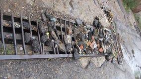 Erosão de água do fundo da estrada Furo do perigo, contexto cinzento de pedra Asfalto quebrado Fluxo obstruído dos restos, a grel imagens de stock