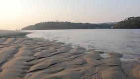 Erosie van de zandige kust door het water op de achtergrond van de rivier Ondiep water stock videobeelden