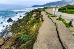Erosievernietiging duidelijk zichtbaar op eenzame kustweg royalty-vrije stock foto