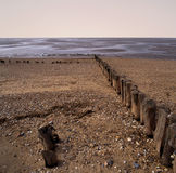 Erosion. Worn sea defences jutting out into sea stock photography