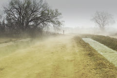 Erosion - Dust Storm. Dust storm over an irrigation ditch showing erosion of top soil from surrounding fields Royalty Free Stock Photos