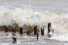 Erosion. Metal groyne posts being eroded by a sea wave. Erosion. Metal groyne posts being eroded and damaged by constant strong wave action royalty free stock image
