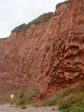 Erosion in the red sandstone coastal cliffs at Budleigh Salterton, Devon, UK and the start of the deserted nudist beach. Erosion in the red sandstone coastal stock photography